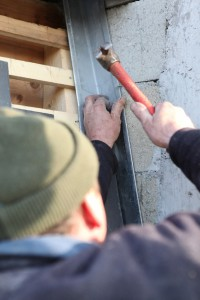 Man is hammering roof flashing
