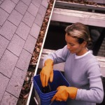 woman cleaning out gutters on roof