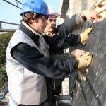 Two roofers putting a new roof on a home