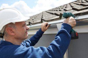 Workman Repairing Guttering On Exterior Of House