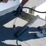 Workers preparing a flat roof covering with a torch